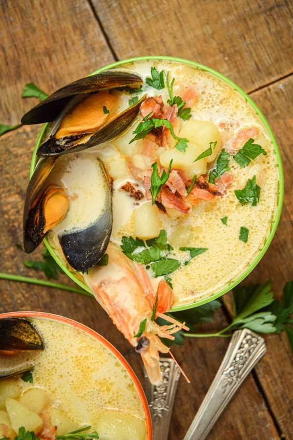 Electric Skillet Seafood Chowder in 2 bowls, wooden background.