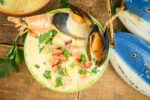 Electric Skillet Seafood Chowder in a bowl, wooden background, wooden fish decoration on the side.