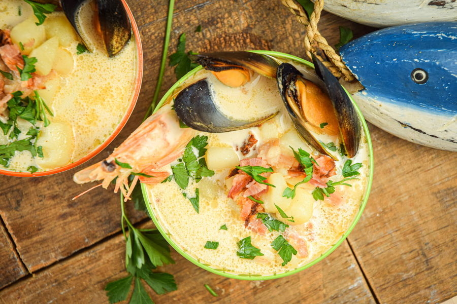 Electric Skillet Seafood Chowder in 2 bowls, wooden background, wooden fish decoration on the side.