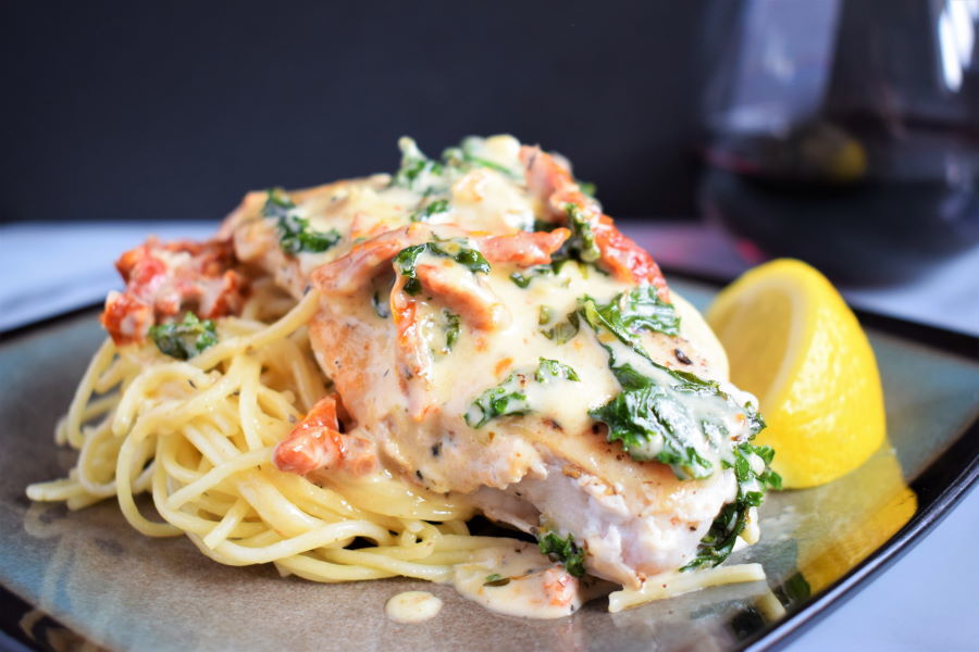 Creamy tuscan chicken and lemon wedge on a plate, dark background, red wine on the side.