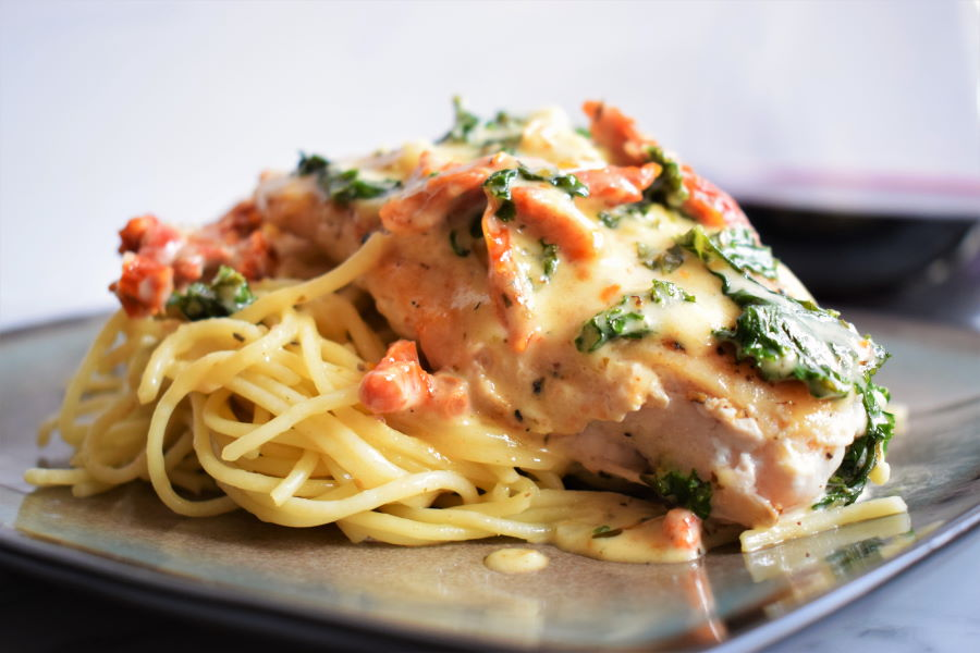 Creamy tuscan chicken on a plate, light background.