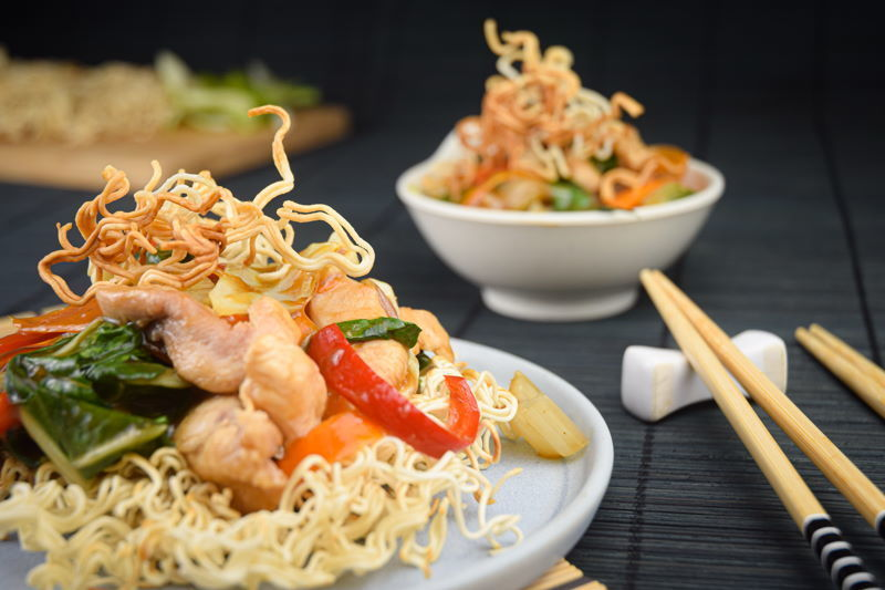 Crunchy chow mein noodles with chopsticks.