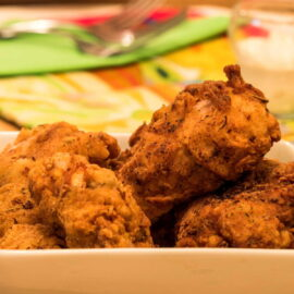Electric skillet fried chicken in a dish.