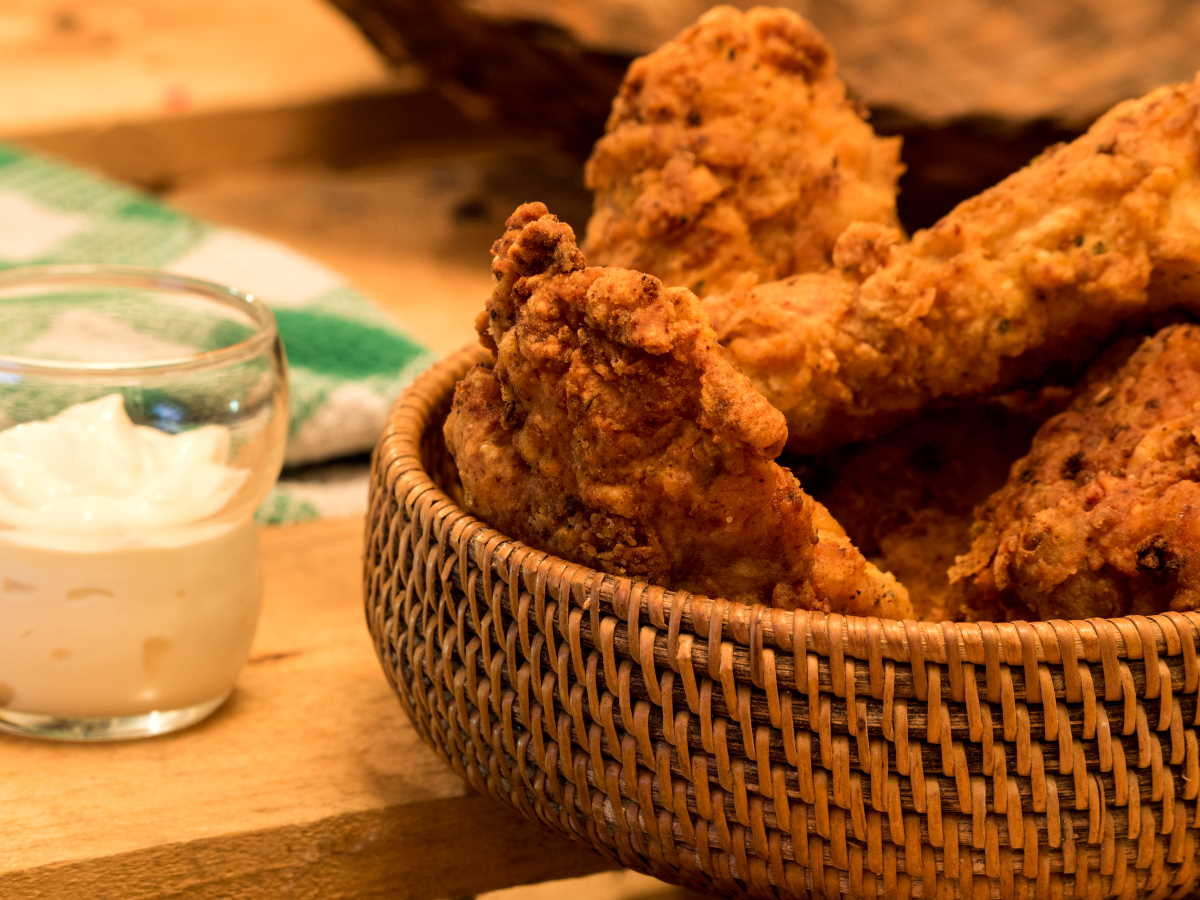 Electric skillet fried chicken in weaved basket.