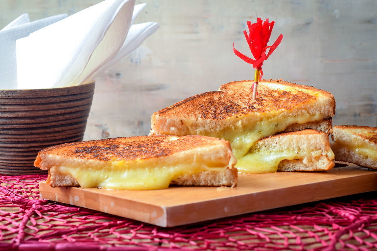 Electric skillet grilled cheese sandwiches on a cutting board over a pink doiley.