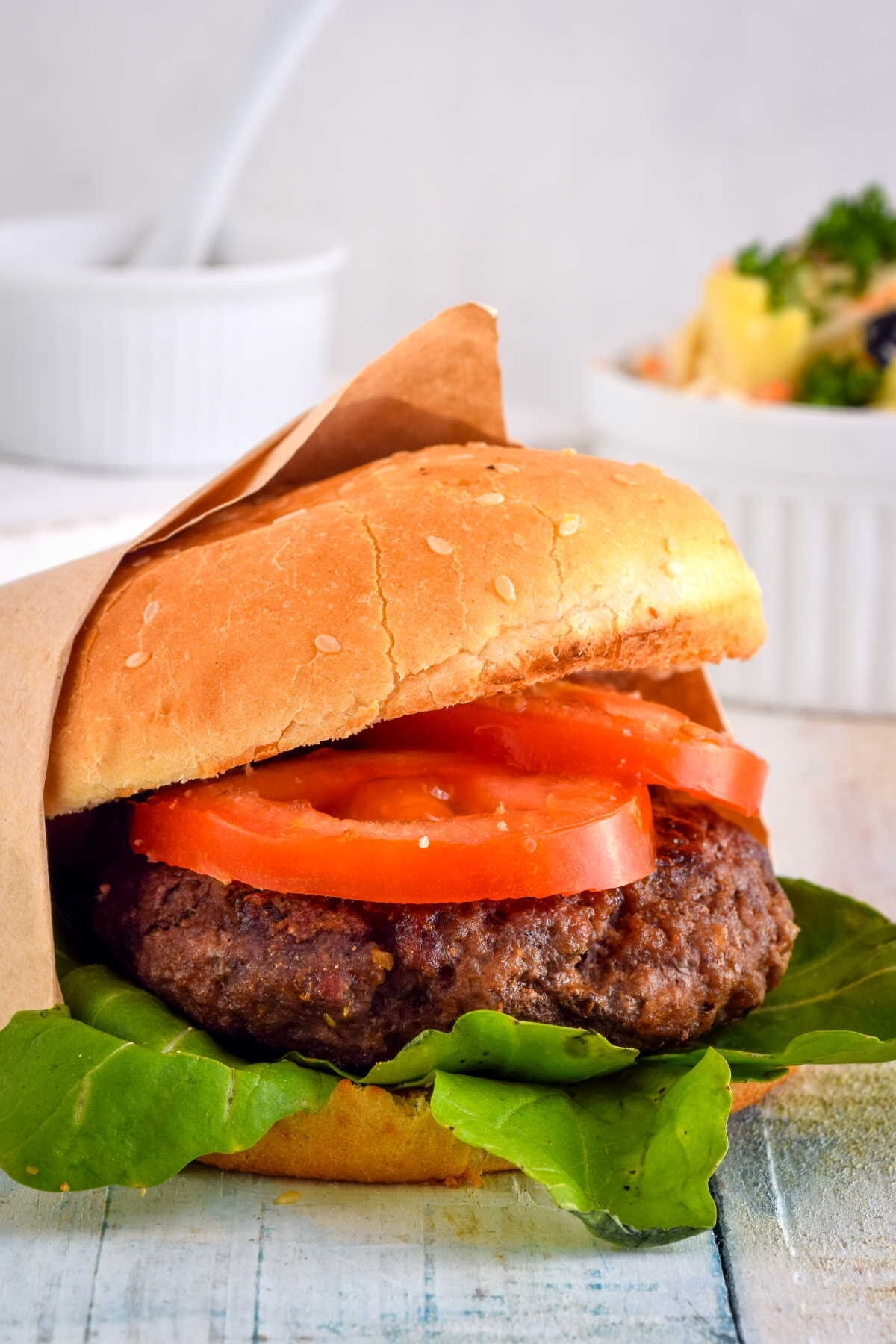 Electric Skillet Hamburgers on wooden background with salad and tortilla chips on the side.
