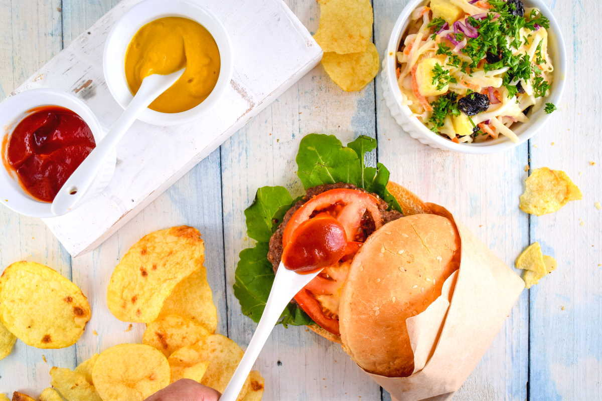 Electric Skillet Hamburgers on wooden background with salad and condiments on the side.