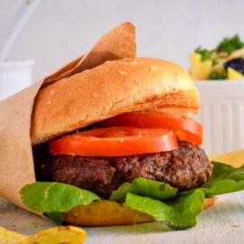 Electric Skillet Hamburgers on wooden background with salad on the side.