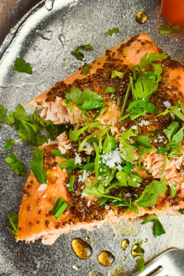 Wild salmon with fresh parsley and tomatoes on a plate.