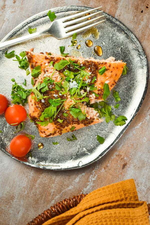 Wild salmon with fresh parsley and tomatoes on a plate with a fork and yellow dish towel.
