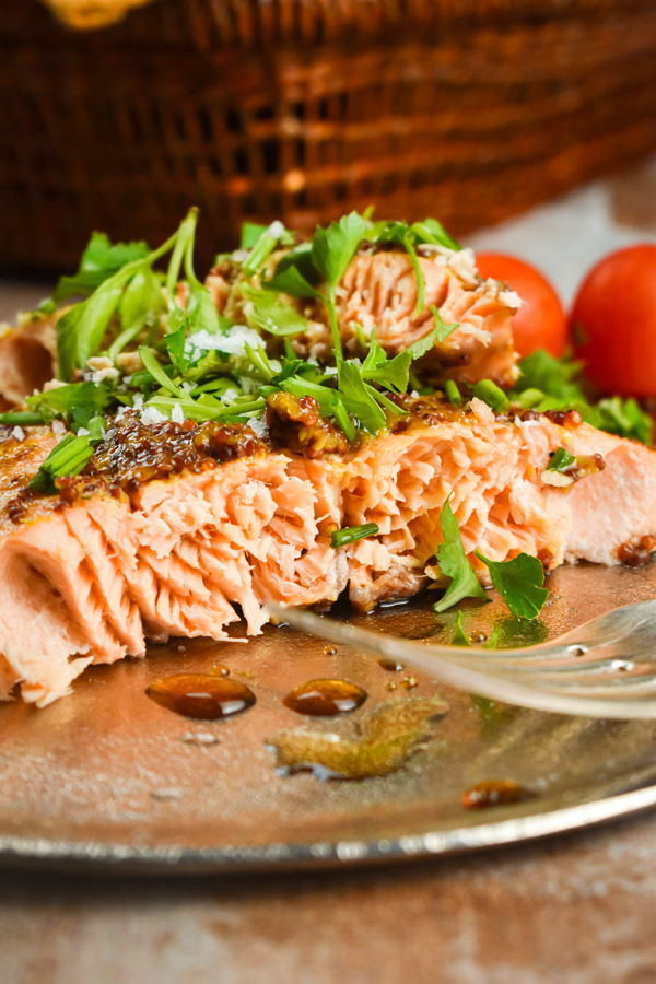Wild salmon with fresh parsley and tomatoes on a plate with a fork.