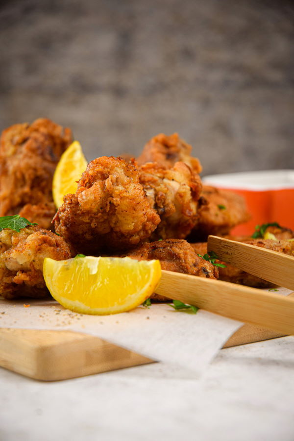 Lemon pepper chicken wings with lemon wedges on wooden cutting board.