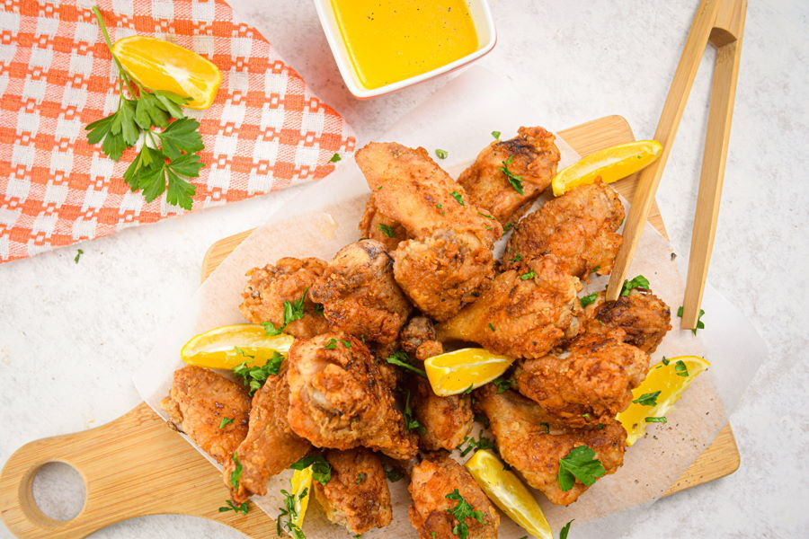 Lemon pepper chicken wings with lemon wedges on wooden cutting board, dipping sauce on the side.