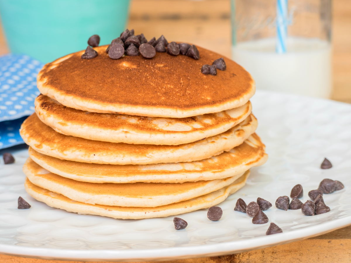 Pancakes piled on a plate with chocolate chips.