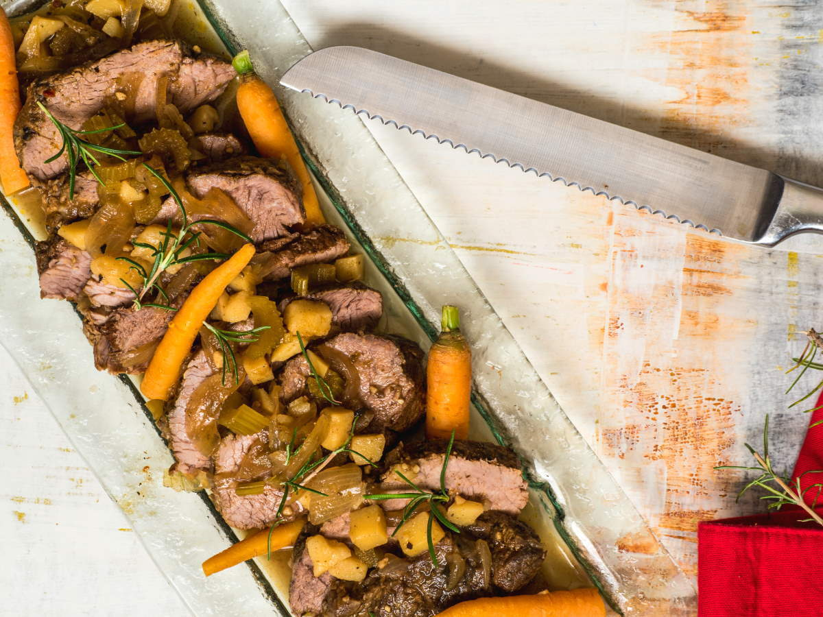 Sliced pot roast on a serving dish with carrots and potatoes.