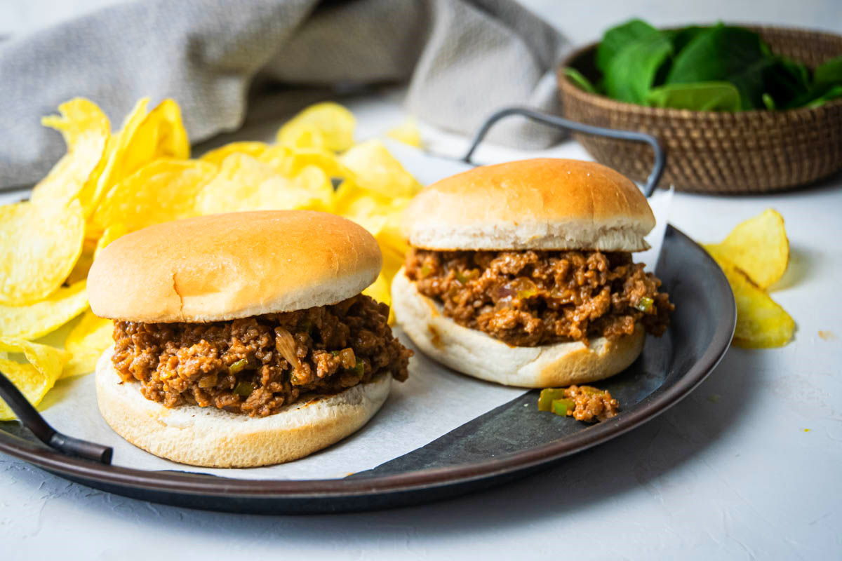 Sloppy Joes on a serving dish with chips and spinach on the side.