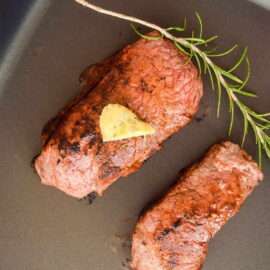 2 steaks in an electric skillet with butter and a rosemary sprig on top.