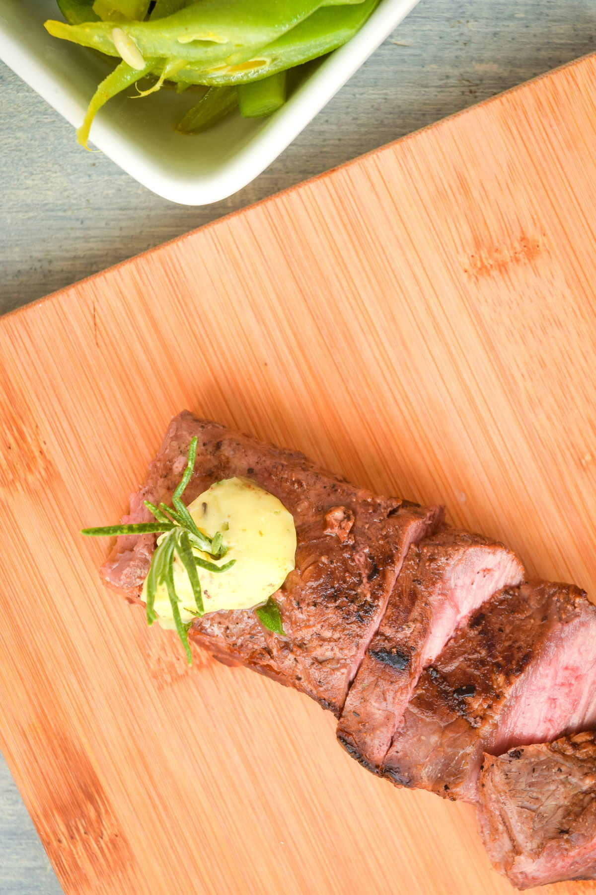 Sliced steak on a cutting board with herb butter.