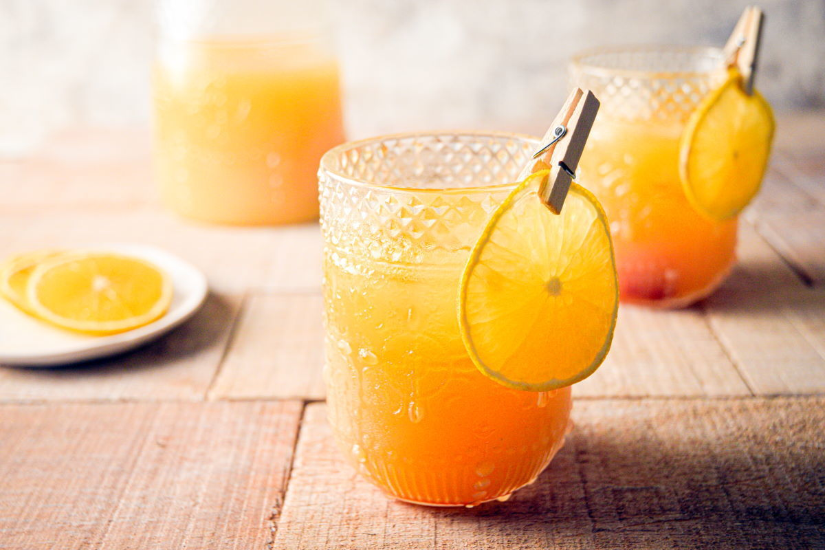 Fall Pumpkin Party Punch in a clear glass with a thin orange slice garnish clipped on with a clothespin, orange slices on a small white plate in the background.