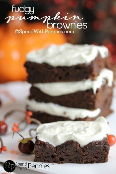 Stacked pumpkin brownies with white frosting.