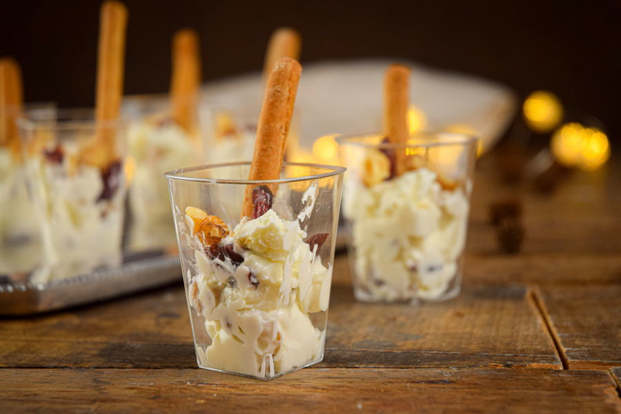 Nutty cranberry goat cheese shots with crispy breadsticks, wooden background.