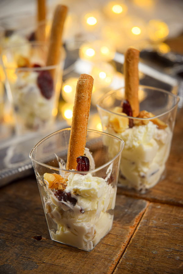 Nutty cranberry goat cheese shots with crispy breadsticks, wooden background and Christmas lights.
