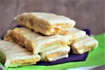Graham wafer lemon bars on a white plate with purple and green napkins.
