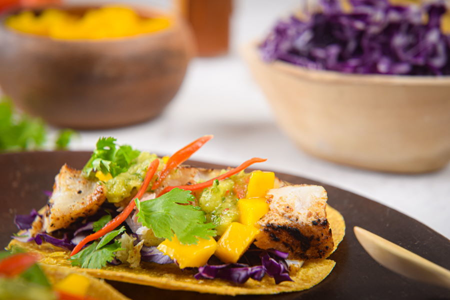 Grilled halibut tacos on brown wooden plate.
