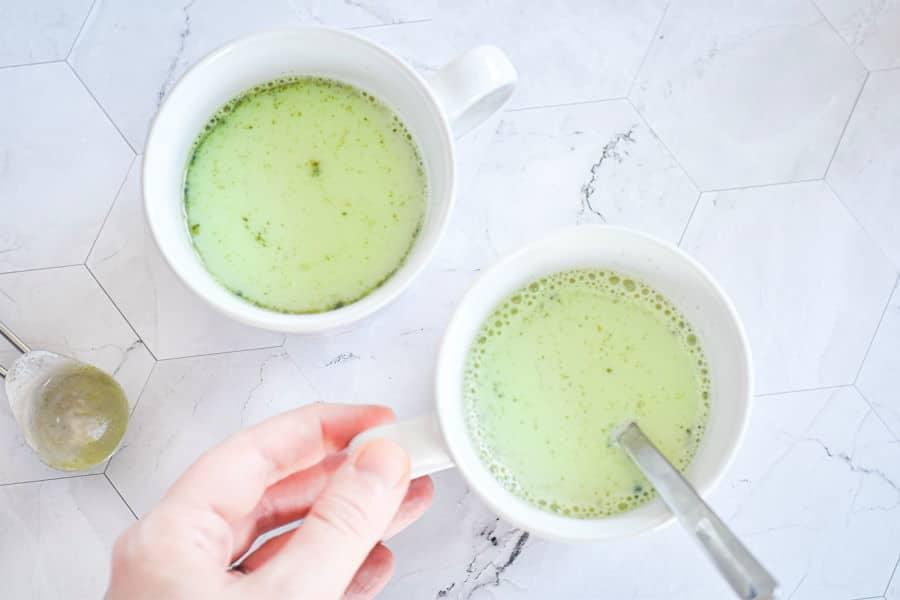 Prepared homemade matcha lattes in 2 white mugs.