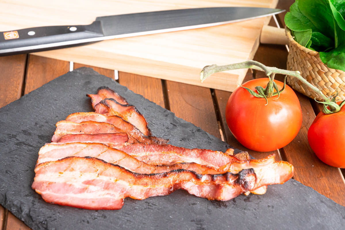 Crispy bacon on a black board, fresh tomatoes and knife on the side.