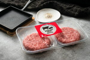 Raw burger patties in a package.