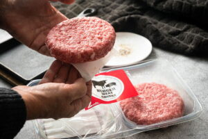 Raw burger patties in a package with paper separators.