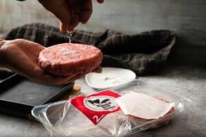 Raw burger patties getting seasoned.