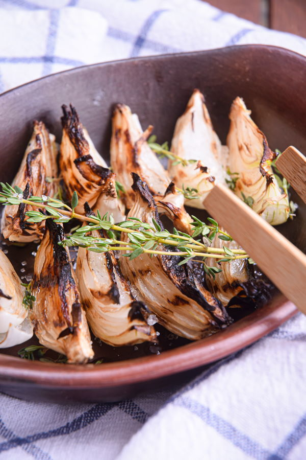 Grilled white onions in wooden bowl.