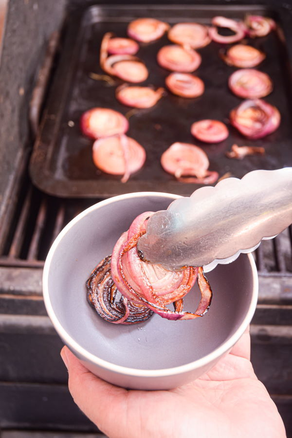 Grilled, sliced red onions on metal baking sheet on grill.