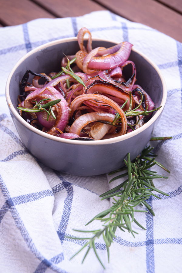Grilled, sliced red onions in bowl.