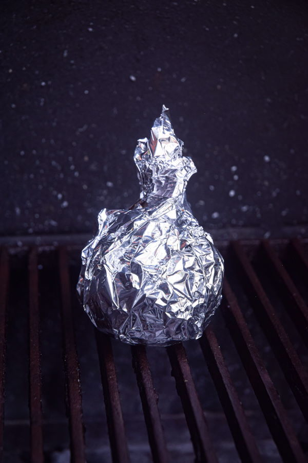 Grilled onion in foil on the grill.