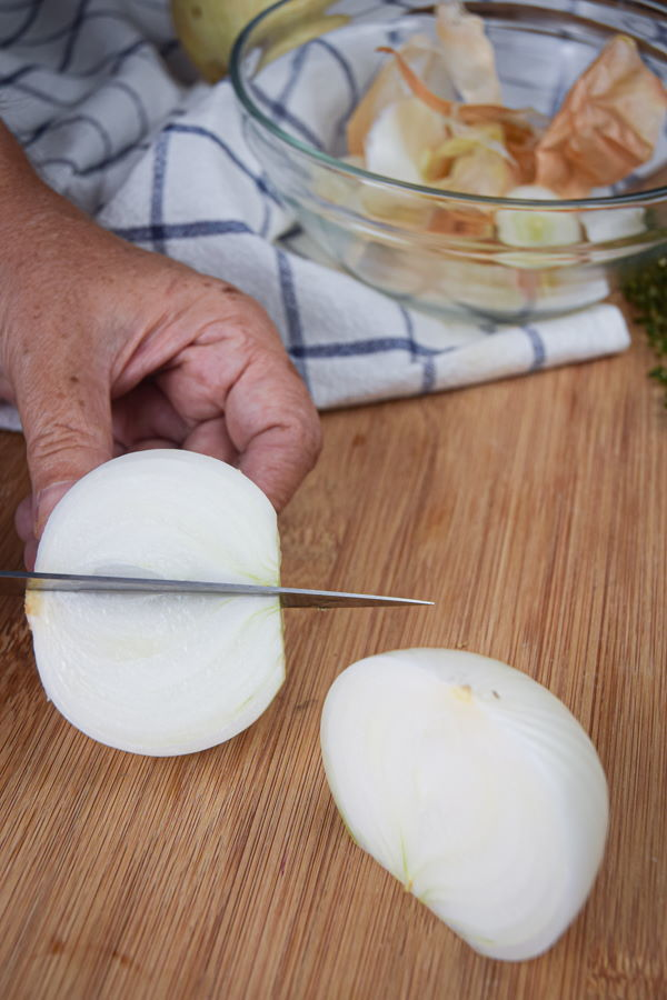 White onion wedges on a wooden cutting board.
