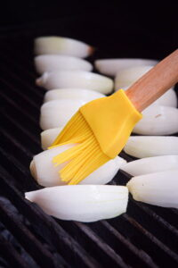 White onion wedges on the grill.