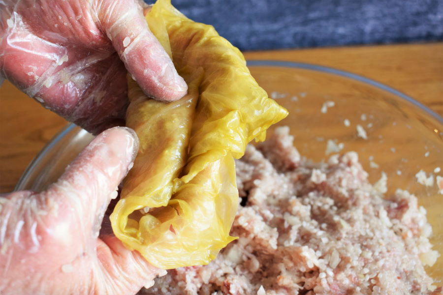 Cabbage roll being rolled up with gloved hands.