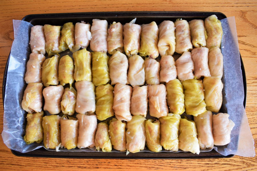 Cabbage rolls on a wax paper-lined baking sheet, on wooden table.
