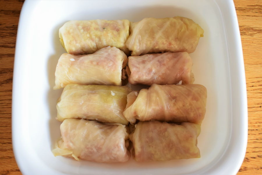 Cabbage rolls in a casserole dish, wooden background.