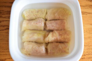 Cabbage rolls in a casserole dish with hot water, wooden background.