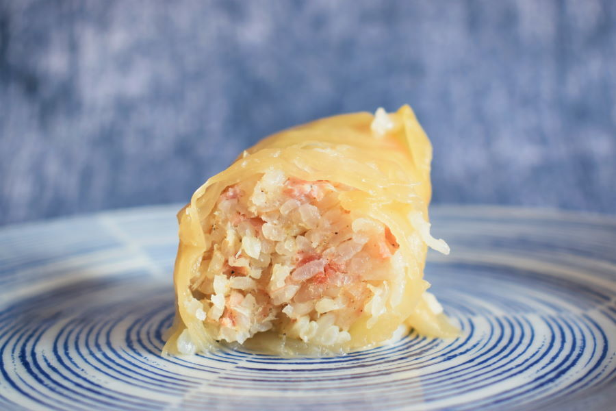 Open cabbage roll on a blue and white plate, blue background.