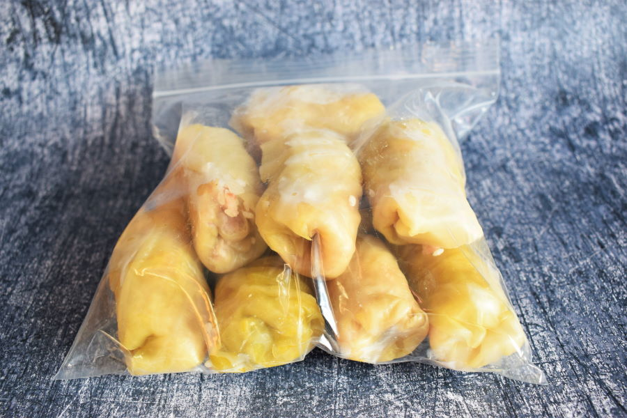 Cabbage rolls in a zip-top bag, blue background.