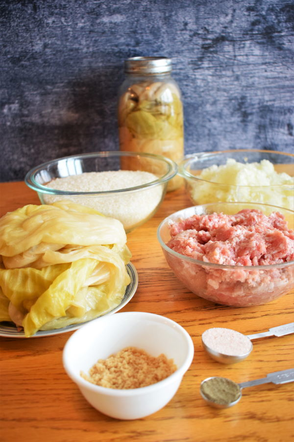 Cabbage roll ingredients on wooden background.