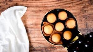 Baked cake balls in cake pop maker, wood background.