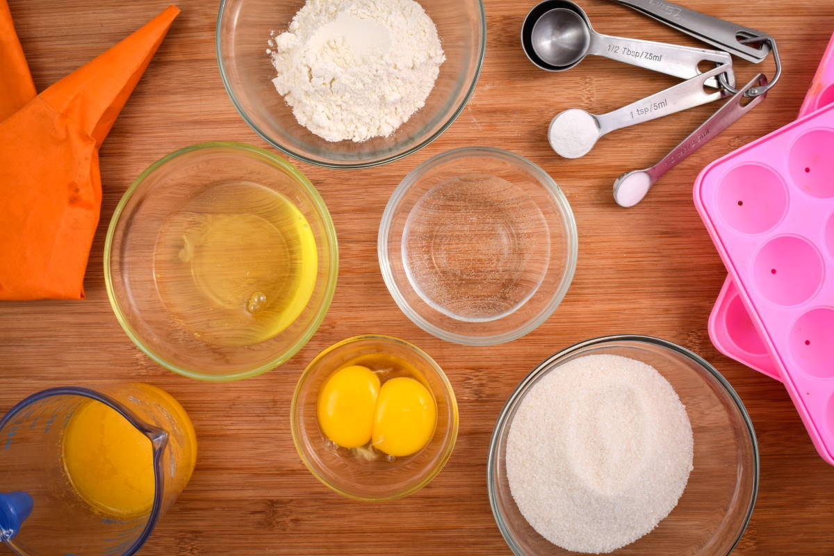 Prepped cake pop ingredients, pink mold and measuring spoons on wooden background.