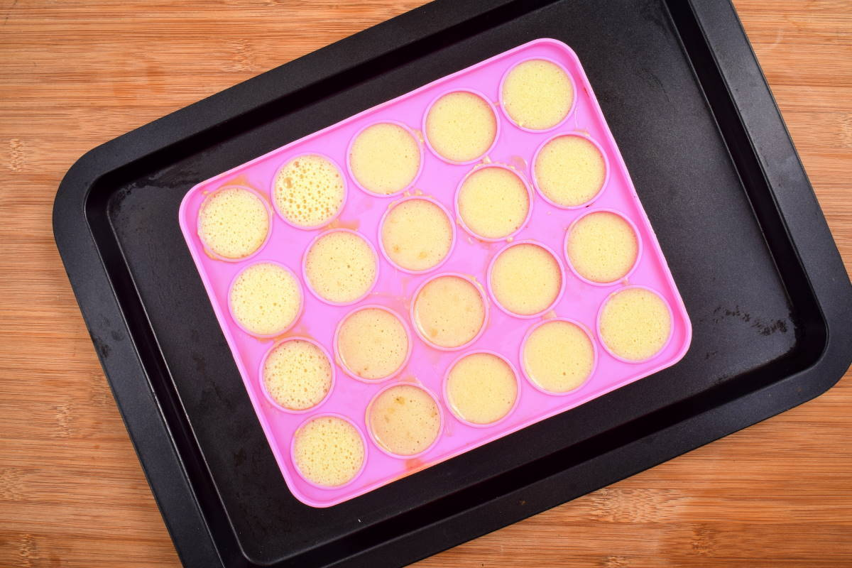 Cake pop mold with batter in it on sheet pan, wooden background.
