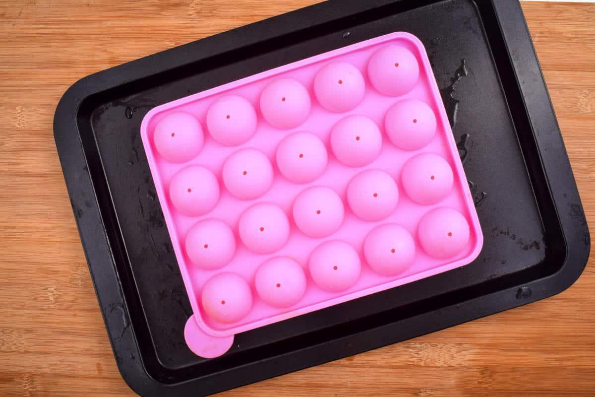 Pink cake pop mold on sheet pan, wooden background.